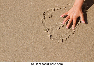 Kid hand drawing a heart in the sand