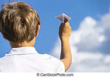 Kid hand with white paper plane against blue sky