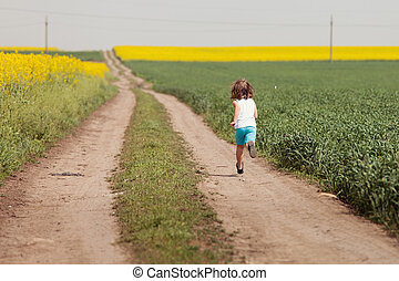 Kid having happy time running on road in the field of...