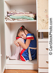 Kid hides in the cupboard.