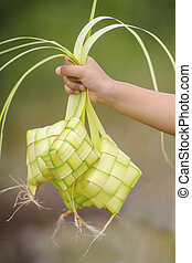 Kid holding a ketupat (rice dumpling) a traditional malay food for eid mubarak.