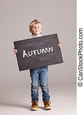 Kid holding board with sign Autumn