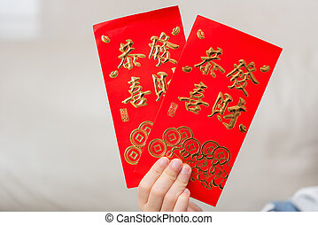 kid holding pair of red pockets written KUNG HEI FAT CHOY translation-wshing you prosperity