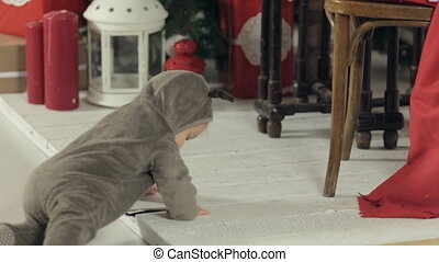 Kid in a suit of New year deer crawling on a wooden white floor