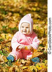 Kid in autumn leaves