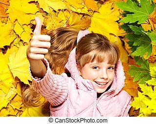 Child in autumn orange leaves. Outdoor.