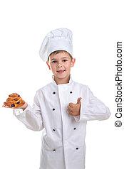 Kid in chef uniform with tasty raisin bun gesturing okay, isolated on white
