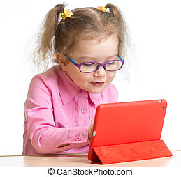 kid in glasses looking at mini tablet pc screen sitting at...