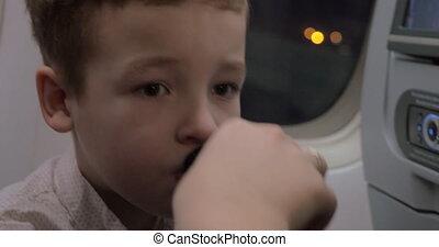 Kid in plane taking medicine