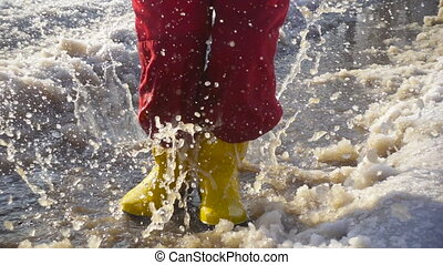 Kid in rainboots jumping in the ice puddle - Kid in yellow...