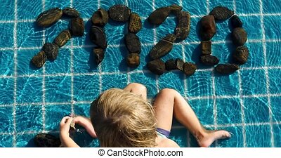 Kid in swimming pool and make pebble rock arranged - Child...