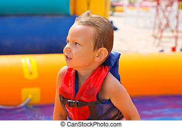 Kid in swimming vest in pool at the water park