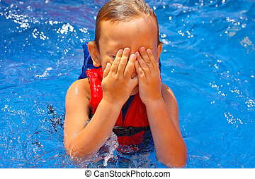 Kid in the swimming pool  covered his face with his hands