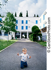 Kid is kneeling on the asphalt against the background of a building and green trees