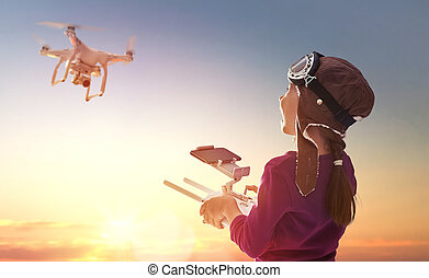 Little girl is operating the drone by remote control in the park. Kid is playing with quadrocopter outdoors.