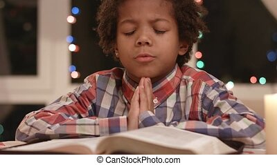 Kid is praying. Boy with closed eyes. Belief and morality....