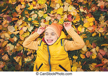 Kid laughing. Happy little child boy lying on autumn leaves, portrait