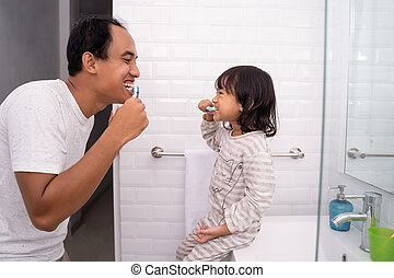 kid learn how to brush teeth with dad