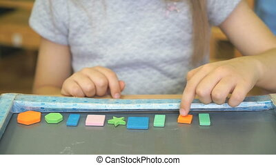 Kid learning counting with colors and shapes - Hands of kid...
