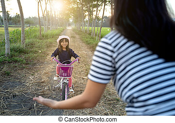 kid learning to ride bicycle with mother