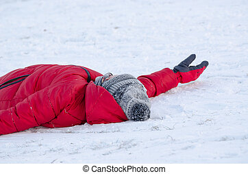 kid lie on snow with red jacket tired from slide - child lie...