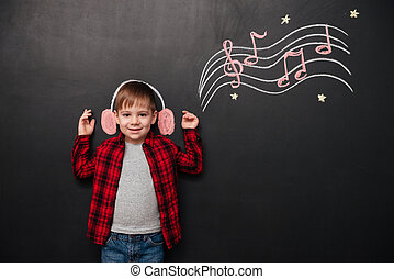 Kid listening to music over black chalk board with drawings
