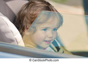 kid looking across a window pane smiling - little cute girl...