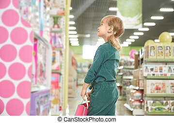 Kid looking at shelves with toys in store.