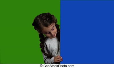 Kid looks out from behind a blue board and shows a thumbs...