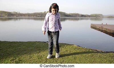 kid loving music near a lake