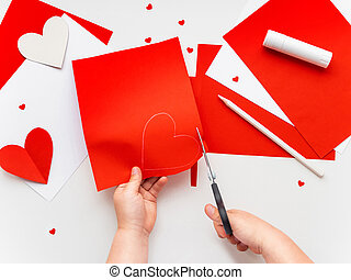 Kid makes Mother's Day or Valentine's Day greeting card. DIY holiday card with red paper volumetric heart, symbol of love. Handicraft made by child with scissors, glue and colored paper. Step 3 of 12