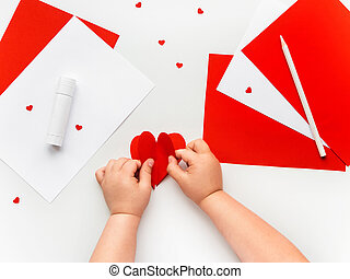 Kid makes Mother's Day or Valentine's Day greeting card. DIY holiday card with red paper volumetric heart, symbol of love. Handicraft made by child with scissors, glue and colored paper. Step 8 of 12