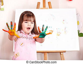 Kid making handprints with paint.