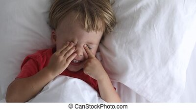 Kid not sleep lies in bed and laughs - Small child lies in...