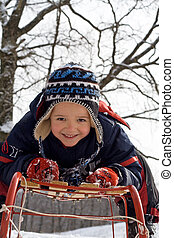 Kid on a sledge - Kid with rosy cheeks laying on a sledge in...