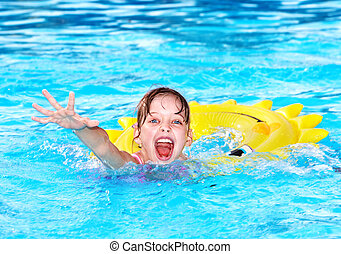 Kid on inflatable ring in swimming pool.