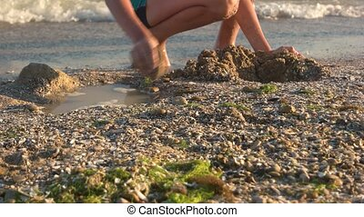 Kid on seashore digging pit. Child playing outdoor, summer.
