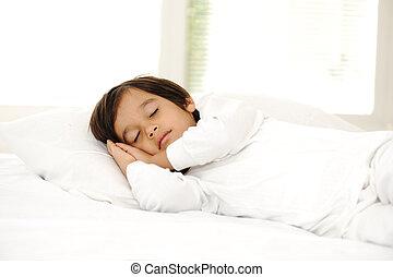 Kid on sleeping bed, happy bedtime in white bedroom
