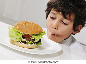 Kid on temptation with delicious hamburger