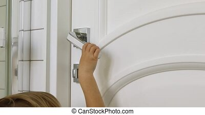 Kid opens door - Small child opens white door to room by...