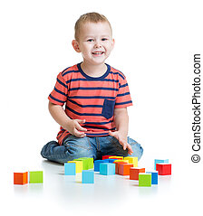 Kid playing and building tower with colorful blocks isolated