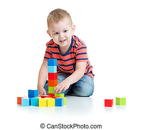 Kid playing and building tower with colorful blocks