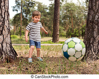 Kid playing football soccer at grass park