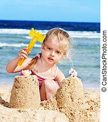Kid playing on beach.