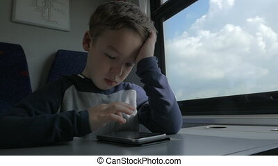 Kid playing on cell when traveling by train - Slow motion...