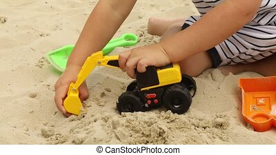kid playing raod works with toy excavatorin in sand - Crop...