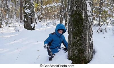 kid playing throwing snowballs from behind tree in winter Park