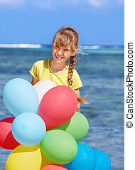 Kid playing with balloons at the beach