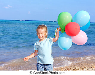 Kid playing with balloons at the beach.