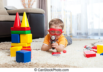 kid playing with building blocks and imagining himself a hero